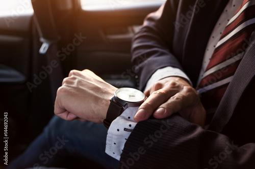 Fotografie, Obraz  Handsome businessman looking on wrist watch in car
