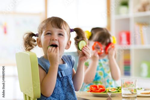 Poster de jardin Magasin alimentation children eating vegetables in kindergarten or at home