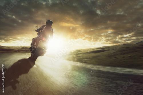 Zdjęcie XXL Motocykl jedzie przez zakręt o zachodzie słońca