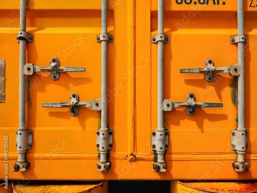Photo  Yellow rusty container door on yard, yellow background