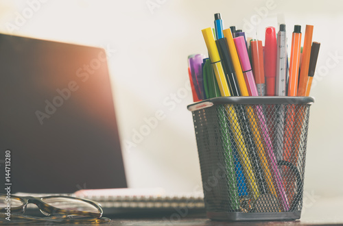 Photo  Colorful pen in metal pen pot and modern laptop
