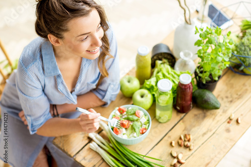 Obraz Young and happy woman eating healthy salad sitting on the table with green fresh ingredients indoors - fototapety do salonu