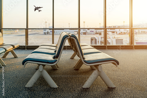 Photo sur Toile Aeroport Empty chairs in the departure hall at airport with airplane taking off at sunset. Travel and transportation in airport concepts.