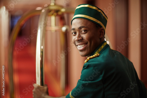 Fotomural Smiley young bellboy pushing cart with luggage