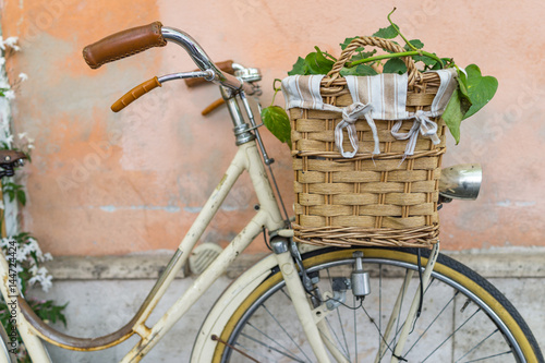 wicker basket with a decoration bouquet of plant on a vintage bicycle with pastel background.