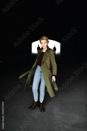 Photo  Beautiful and attractive young blonde actress celebrity girl in stylish coat and hipster boots escaping from dark tunnel with two extraterrestrial invaders on background