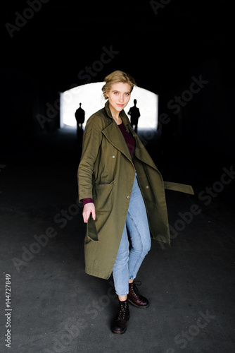 Beautiful and attractive young blonde actress celebrity girl in stylish coat and hipster boots escaping from dark tunnel with two extraterrestrial invaders on background Wallpaper Mural