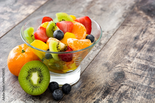 Foto op Aluminium Vruchten Fruit salad in crystal bowl on wooden table