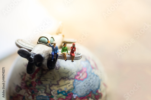 Miniature people : business team sitting on airplane wing