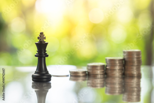 Chess pieces with coins stacks as backdrop, business