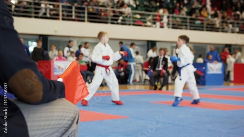 Photo  Martial art competitions- karate - judge coaches looking at female teenager's ka