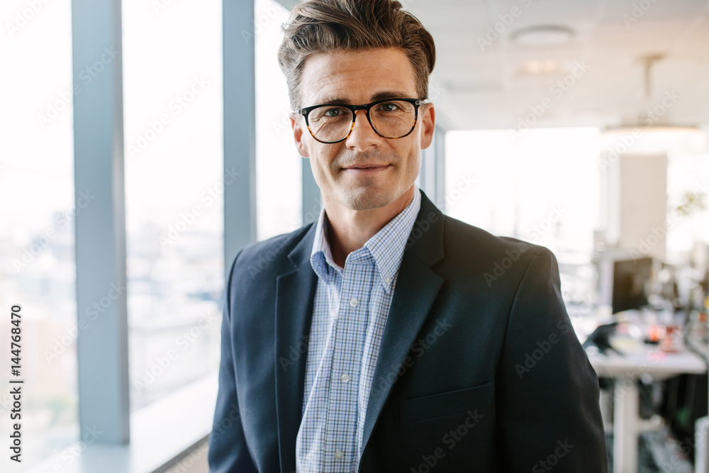 Fototapeta Confident mature businessman standing in office