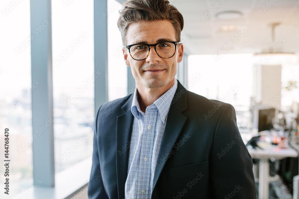 Fototapeta Confident mature businessman standing in office