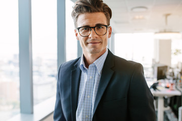 Confident mature businessman standing in office