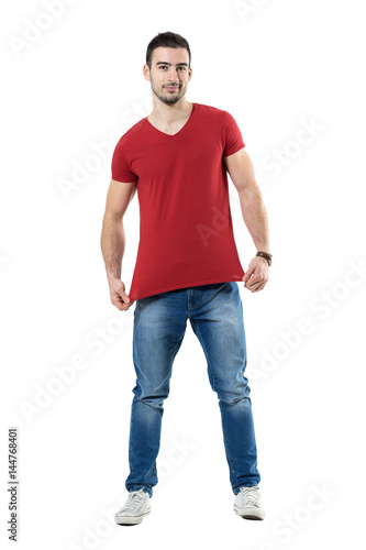 32b03488 Young man stretching and showing red t-shirt blank copy space. Full body  length portrait isolated over white studio background.