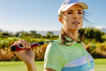 Young woman standing on golf course.