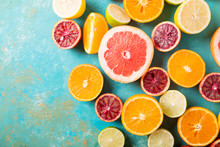 Citrus Fruits On Turquoise Abstract Background. Оrange, Lemon, Grapefruit, Mandarin, Lime. Mixed Festive Colorful Tropical And Citrus Fruit Sliced. Healthy Eating Photo Concept. Copyspace
