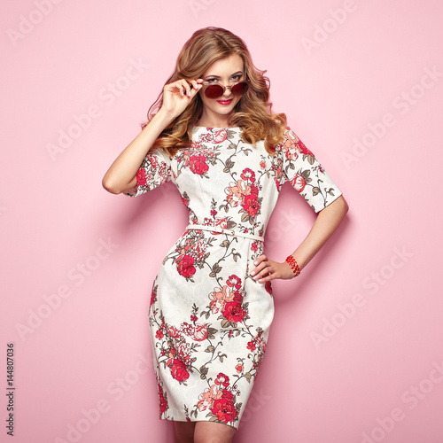 Blonde young woman in floral spring summer dress. Girl posing on a pink background. Summer floral outfit. Stylish wavy hairstyle. Fashion photo. Glamour lady in stylish sunglasses Wall mural