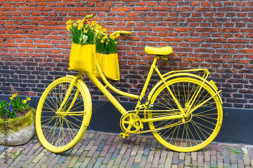Foto op Plexiglas Fiets Vintage yellow bicycle with basket of daffodil flowers on old rustic brick wall background