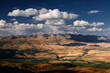 A top view to highland steppe plateau valley with yellow grass and trees on a background of dramatic mountains ridges ranges under clouds and blue sky, Kurai, Altai, Siberia, Russia