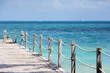 Long wooden pier and the turquoise water of the Caribbean sea.