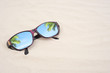 Holiday travel sunglasses on sand beach. Empty space you can place your text or information.