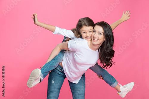 Obraz na plátně Happy mother piggybacking adorable little daughter smiling at camera