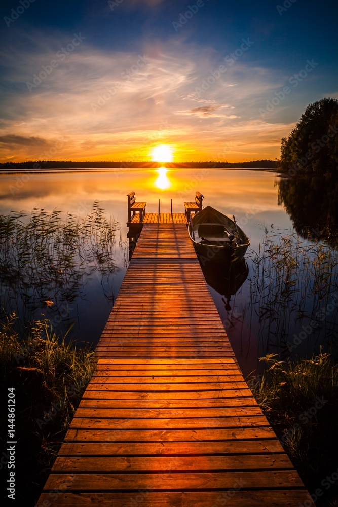 Fototapeta Sunset over the fishing pier at the lake in Finland