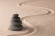 balancing black rocks in zen sand garden. Stone pile stacked in balance. Spa wellness or yoga background...