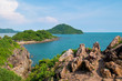 View from the mountain peak along blue sea and high rocks against sky. Colorful mountain landscape. Vacation on seashore. Summer travel in Thailand.