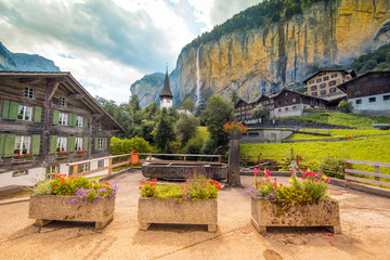 The picturesque landscape with flowers, a waterfall and canyon church in Lauterbrunnen in the Swiss Alps, Switzerland, Europe