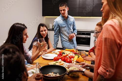 Zdjęcie XXL Grupa przyjaciele w kuchni przygotowywa wpólnie jarskiego posiłek. Domowy przyjęcie.