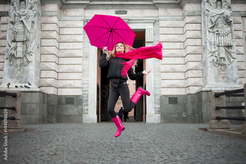 Stampa su Tela  Beautiful young and happy blond woman with colorful umbrella on the street
