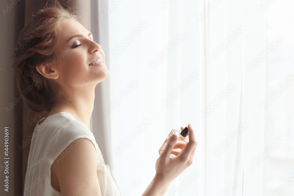 Fototapety, obrazy: Beautiful young woman with bottle of perfume near window at home