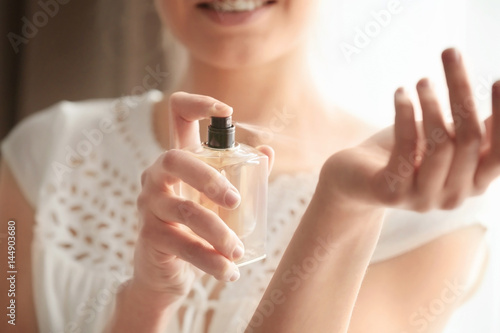 Fototapeta Beautiful young woman with bottle of perfume at home, closeup obraz