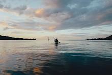 People Kayaking On The Water At Sunset