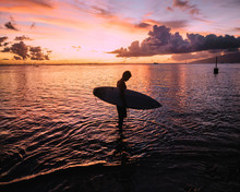 Man By Shoreline Holding Surfboard At Sunset, Tahiti, South Pacific
