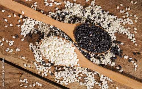 Fresh black and white sesame seeds in spoons