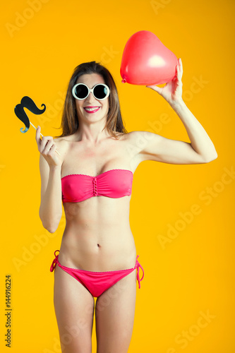 Fotografie, Obraz Beautiful brunette woman in pink bikini playing with red heart shape balloon isolated on yellow background