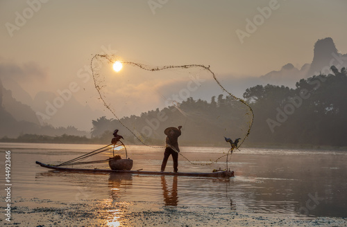 Foto op Canvas Guilin Cormorant fisherman throws a net with ancient traditional chinese bamboo boats at sunrise - Xingping, China