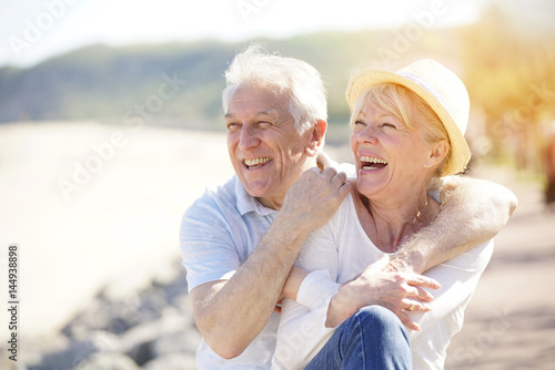 Fotografía  Senior couple relaxing by the sea on sunny day