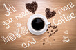 Hot cup of espresso and heart shape made from coffee beans on wooden surface. Sign: All you need is love and more coffee.