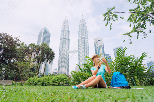 Travel concept. Pretty young woman in hat using smartphone while sitting on the grass against Petrones Twins Tower in Kuala-Lumpur.