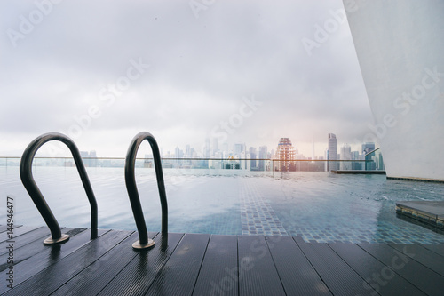 Plagát Swimming pool on roof top with beautiful city view