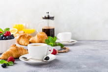 White Cups Of Coffee And Croissants On Light Gray Background, Selective Focus. Healthy Breakfast Concept With Copy Space.
