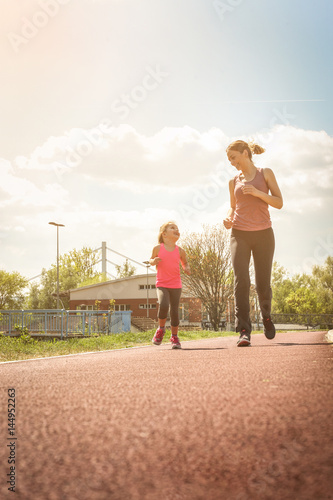 Staande foto Jogging Caucasian mother and daughter jogging outdoors.