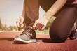 Sportswoman tying laces on sneakers.