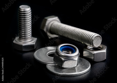 screw isolated on the black backgrounds. Nuts with bolts and washers closeup