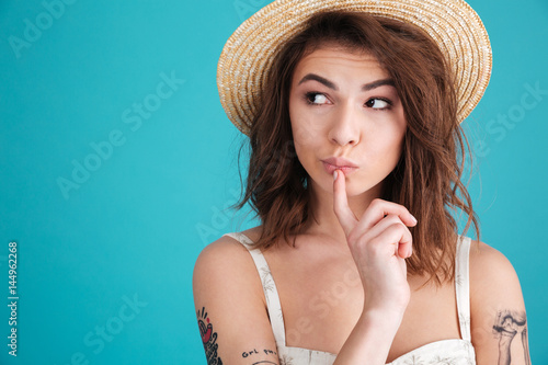 Canvastavla Thoughtful young woman in straw hat wondering and looking away