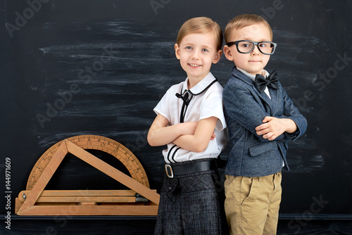 Little girl and boy against blackboard. School concept